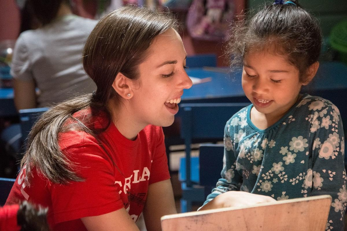 A volunteer reads a book to a young girl at a volunteer teaching placement in Costa Rica